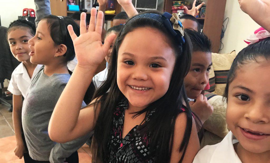 Niños levantando la mano