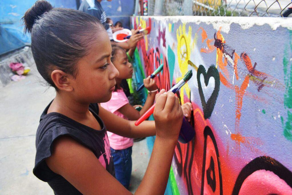 Niñas pintando mural